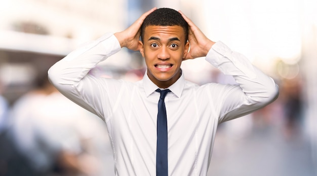 Junger afroamerikanischer geschäftsmann nimmt hände auf kopf, weil migräne in der stadt hat
