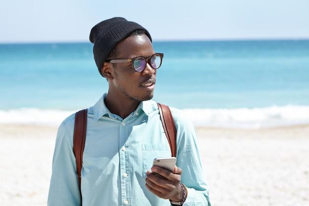 Junger afroamerikanischer hipster, der textnachrichten auf smartphone während des entspannens am meer zur tageszeit schreibt. stilvoller schwarzer mann, der elektronisches gerät am strand, am blauen ozean und am weißen sand im horizont verwendet
