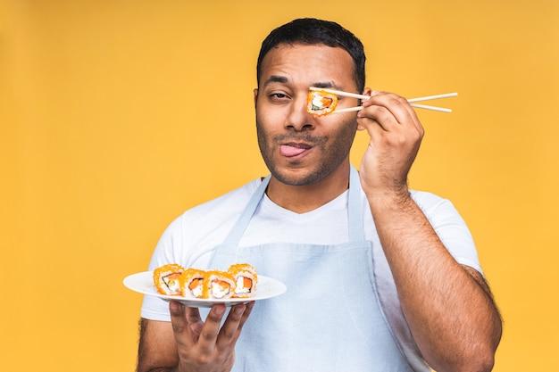 Junger afroamerikanischer indischer schwarzer mann, der sushi mit stäbchen über isoliertem gelbem hintergrund isst. kochen sie sushi zubereiten.