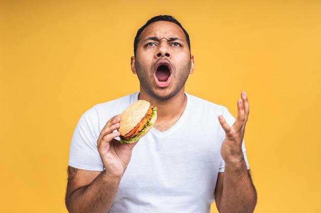 Junger afroamerikanischer indischer schwarzer mann isst hamburger isoliert über gelbem hintergrund. diät-konzept.