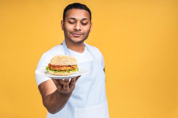 Junger afroamerikanischer indischer schwarzer mann isst hamburger isoliert über gelbem hintergrund. kochen sie, das burger zubereitet.