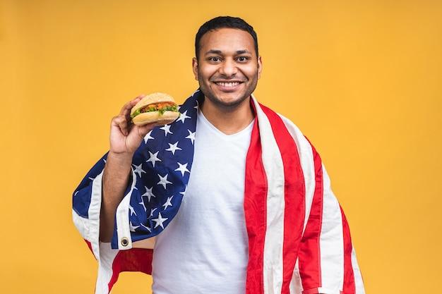 Junger afroamerikanischer indischer schwarzer mann isst hamburger isoliert über gelbem hintergrund mit amerikanischer flagge. diät-konzept.