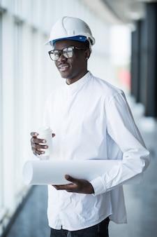 Junger afroamerikanischer ingenieur mit blaupausen vor panoramafenstern im büro