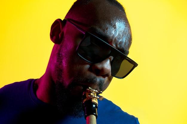 Junger afroamerikanischer jazzmusiker, der das saxophon auf gelbem hintergrund im trendigen neonlicht spielt.