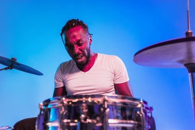Junger afroamerikanischer jazzmusiker oder schlagzeuger, der schlagzeug auf blauem studiohintergrund in trendigen neonlichtern spielt. konzept von musik, hobby, inspiration. buntes porträt des fröhlichen künstlers.