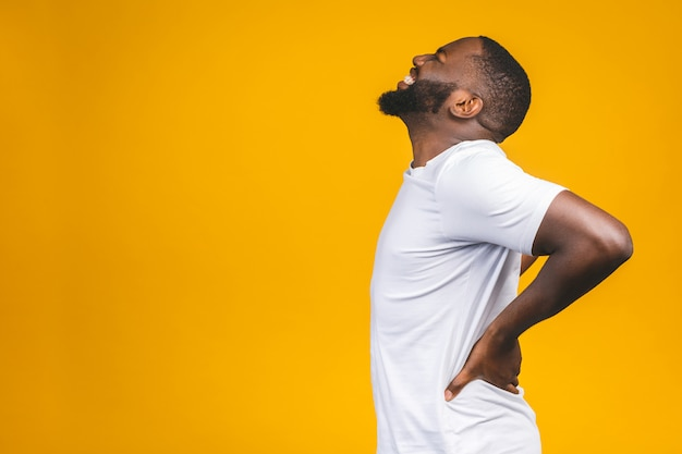 Junger afroamerikanischer junger mann, der unter rückenschmerzen leidet, weil er sich an isolierter wand bemüht hat.