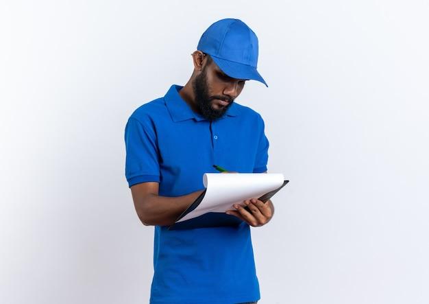 Junger afroamerikanischer lieferbote, der etwas in die zwischenablage schreibt, isoliert auf weißer wand mit kopierraum