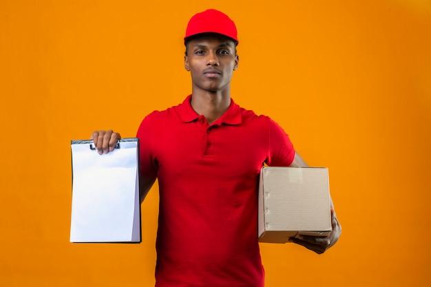 Junger afroamerikanischer lieferbote, der rotes poloshirt und kappe hält boxpaket und zwischenablage mit leeren rohlingen trägt, die zuversichtlich über isoliertem orange schauen
