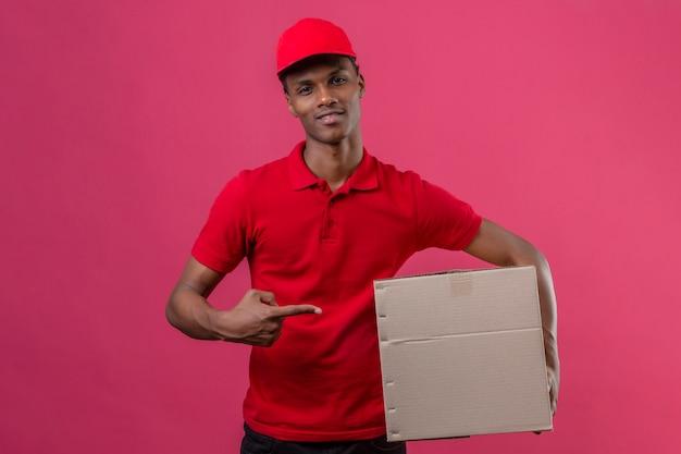 Junger afroamerikanischer lieferbote, der rotes poloshirt und kappe hält, die karton hält und auf kasten mit finger zeigt, der über lokalisiertem rosa lächelt