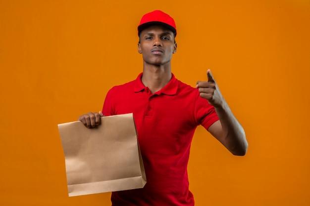 Junger afroamerikanischer lieferbote, der rotes poloshirt und kappe hält, die papiertüte mit essen zum mitnehmen zeigt, das mit finger auf kamera mit ernstem gesicht über isoliertem orange zeigt