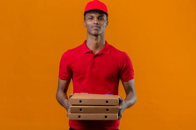 Junger afroamerikanischer lieferbote, der rotes poloshirt und kappe hält, die stapel des positiven ausdrucks der pizzaschachteln über isoliertem orange halten