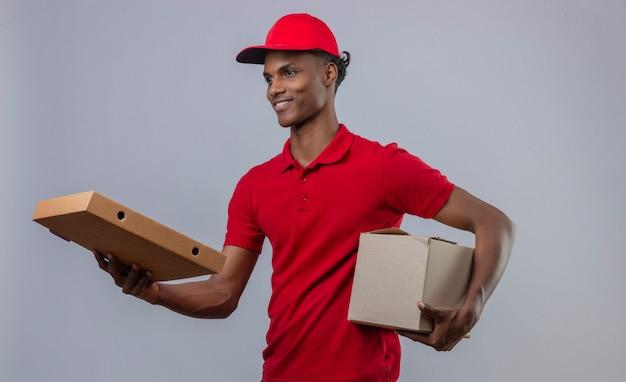 Junger afroamerikanischer lieferbote, der rotes poloshirt und kappe hält, die stapel von pappkartons lächelnd und pizzaschachtel zum kunden über isoliertem weiß hält