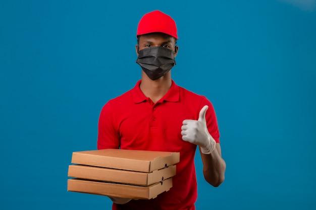 Junger afroamerikanischer lieferbote, der rotes poloshirt und kappe in der schutzmaske und in den handschuhen trägt, die mit stapel von pizzaschachteln stehen, die daumen oben über lokalisiertem blau zeigen