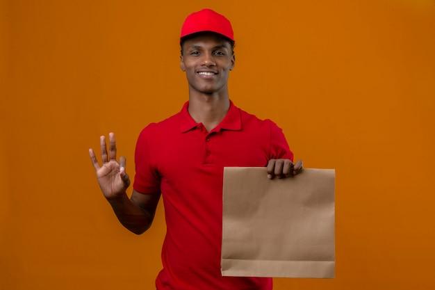 Junger afroamerikanischer lieferbote, der rotes poloshirt und kappe mit papiertüte mit essen zum mitnehmen trägt, das ok zeichen oder nummer drei mit fingern über isoliertem orange macht