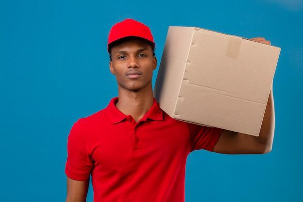 Junger afroamerikanischer lieferbote, der rotes poloshirt und kappe trägt, die mit kasten auf schulter sicher steht, die über isoliertes blau schaut