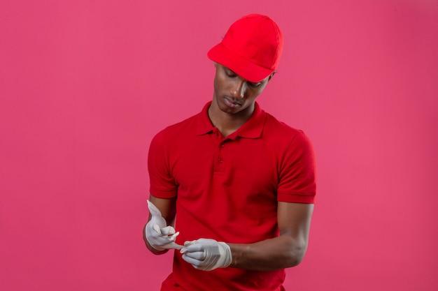 Junger afroamerikanischer lieferbote, der rotes poloshirt und kappe trägt, die schutzhandschuhe über isoliertem rosa abnehmen