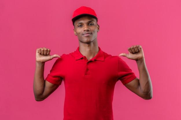 Junger afroamerikanischer lieferbote, der rotes poloshirt und kappe trägt, die sicher schauen, mit den fingern zu sich über lokalisiertem rosa zeigend