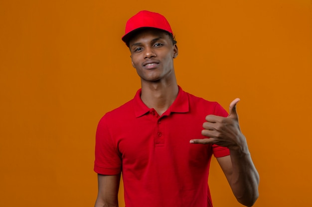 Junger afroamerikanischer lieferbote, der rotes poloshirt und kappe trägt, die zuversichtlich macht, telefongeste zu machen, rufen mich zurück zeichen über isolierte orange