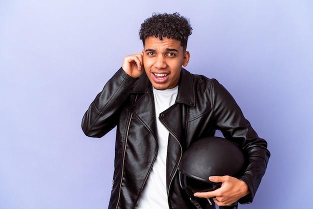 Junger afroamerikanischer lockiger biker-mann isoliert, der ohren mit händen bedeckt.