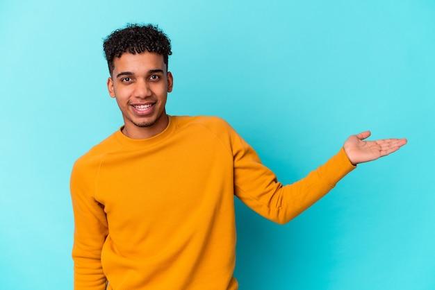 Junger afroamerikanischer lockiger mann auf blau, der einen kopienraum auf einer handfläche zeigt und eine andere hand auf taille hält.