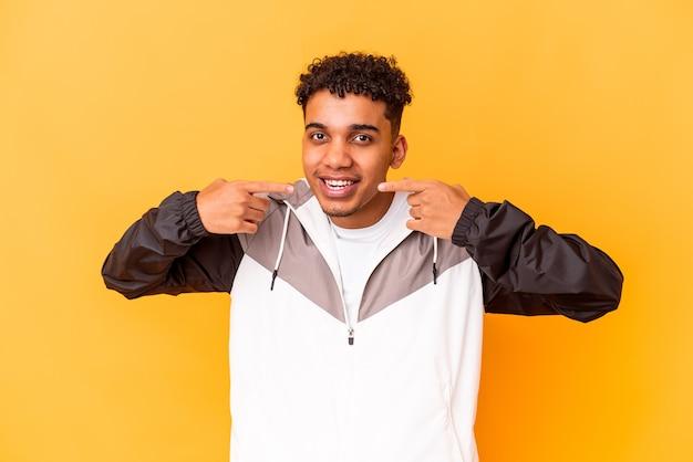Junger afroamerikanischer lockiger mann isoliert auf violettem lächeln und zeigt mit den fingern auf den mund.