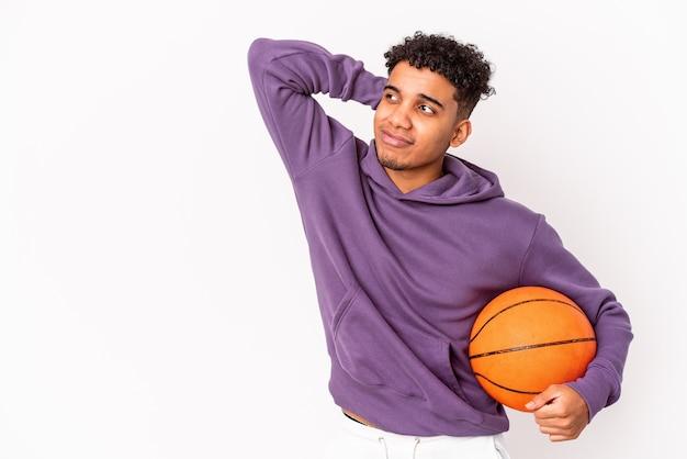 Junger afroamerikanischer lockiger mann isoliert, der basketball spielt, der den hinterkopf berührt, denkt und eine wahl trifft.