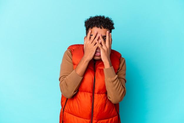 Junger afroamerikanischer lockiger mann lokalisiert auf blauem blinzeln an der kamera durch finger, verlegenes bedeckendes gesicht.