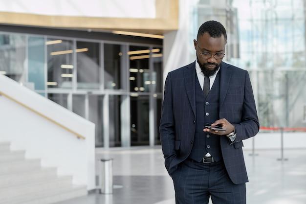 Junger afroamerikanischer makler im anzug sms im smartphone