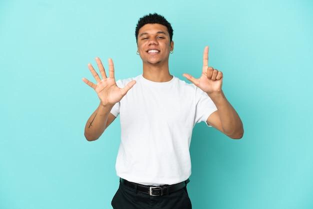 Junger afroamerikanischer mann auf blauem hintergrund isoliert, der mit den fingern sieben zählt