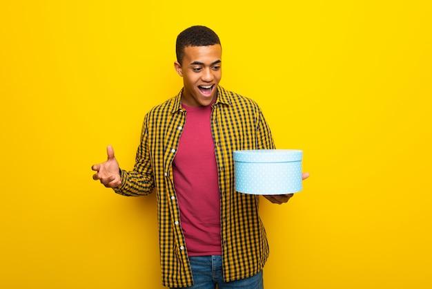 Junger afroamerikanischer mann auf dem gelben hintergrund, der geschenkbox in den händen hält
