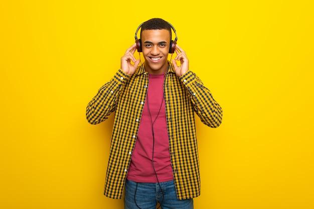 Junger afroamerikanischer mann auf dem hören musik mit kopfhörern