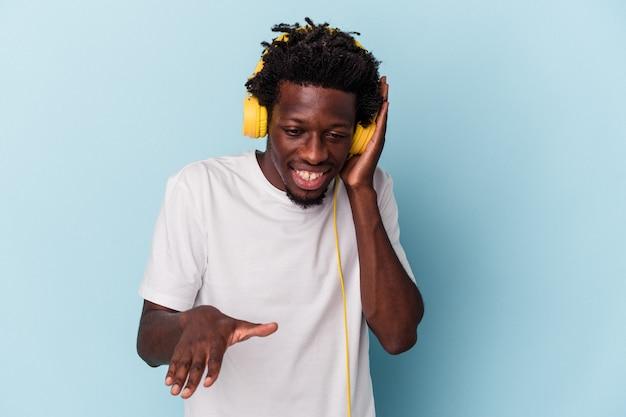 Junger afroamerikanischer mann, der auf blauem hintergrund musik hört, die mit ausgestreckter hand steht und ein stoppschild zeigt, um sie zu verhindern.