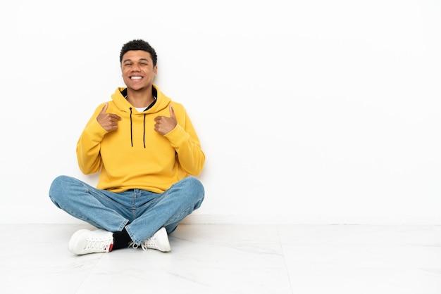 Junger afroamerikanischer mann, der auf dem boden lokalisiert auf weißem hintergrund mit überraschtem gesichtsausdruck sitzt