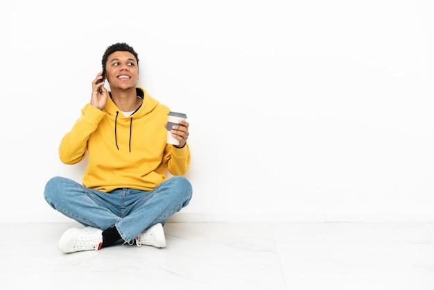 Junger afroamerikanischer mann, der auf dem boden sitzt, isoliert auf weißem hintergrund, der kaffee zum mitnehmen und ein handy hält