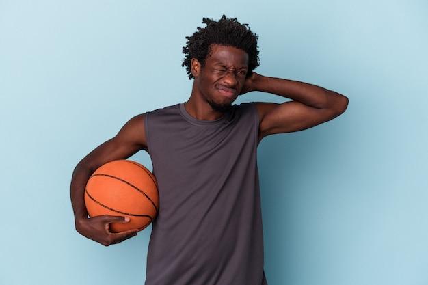 Junger afroamerikanischer mann, der basketball spielt, isoliert auf blauem hintergrund, der den hinterkopf berührt, nachdenkt und eine wahl trifft.