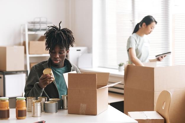 Junger afroamerikanischer mann, der bei wohltätigkeits- und spendenveranstaltungen konserven in kisten verpackt, kopierraum