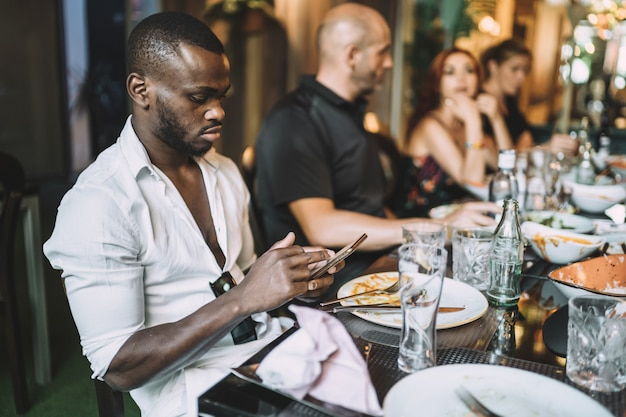 Junger afroamerikanischer mann, der beim essen mit seinen freunden sein telefon benutzt