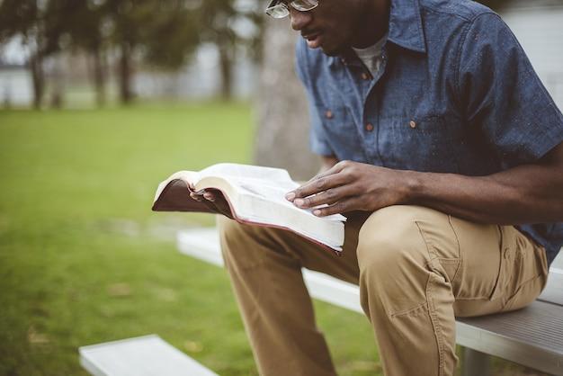 Junger afroamerikanischer mann, der die bibel in einem park sitzt und liest
