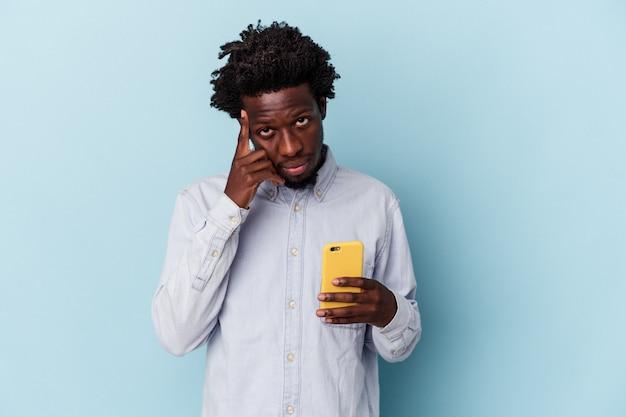 Junger afroamerikanischer mann, der ein mobiltelefon isoliert auf blauem hintergrund hält und mit dem finger auf den tempel zeigt, denkt, konzentriert sich auf eine aufgabe.