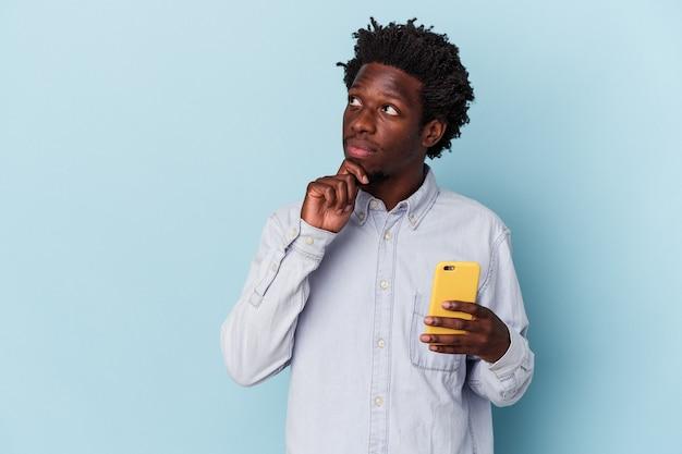 Junger afroamerikanischer mann, der ein mobiltelefon isoliert auf blauem hintergrund hält und seitlich mit zweifelhaftem und skeptischem ausdruck schaut.