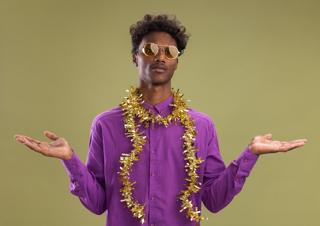 Junger afroamerikanischer mann, der eine brille mit lametta-girlande um den hals trägt, die leere hände lokalisiert auf olivgrüner wand zeigt