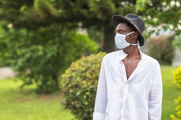 Junger afroamerikanischer mann, der eine schützende gesichtsmaske trägt und im freien posiert