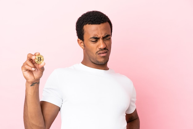 Junger afroamerikanischer mann, der einen bitcoin über isoliertem rosa hintergrund hält und unter rückenschmerzen leidet, weil er sich bemüht hat