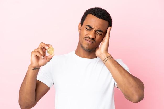 Junger afroamerikanischer mann, der einen bitcoin über isoliertem rosa hintergrund mit kopfschmerzen hält