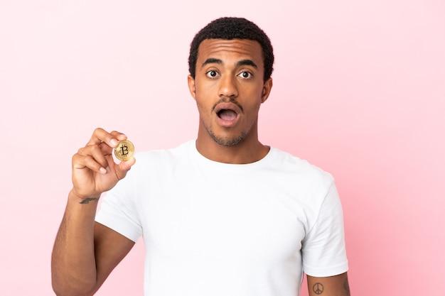 Junger afroamerikanischer mann, der einen bitcoin über isoliertem rosa hintergrund mit überraschendem gesichtsausdruck hält