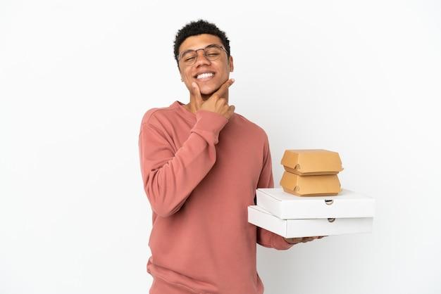 Junger afroamerikanischer mann, der einen burger und pizzas isoliert auf weißem hintergrund hält, glücklich und lächelnd