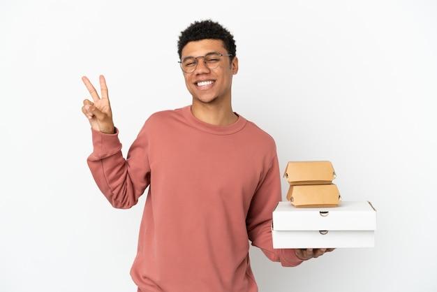 Junger afroamerikanischer mann, der einen burger und pizzas isoliert auf weißem hintergrund hält, lächelt und zeigt victory-zeichen