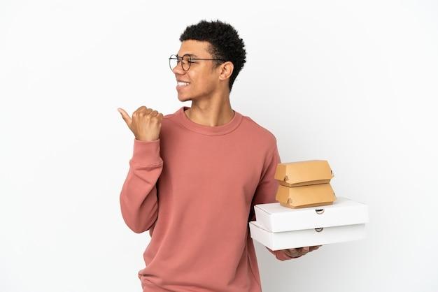Junger afroamerikanischer mann, der einen burger und pizzas isoliert auf weißem hintergrund hält und auf die seite zeigt, um ein produkt zu präsentieren