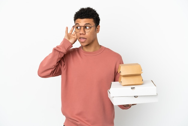 Junger afroamerikanischer mann, der einen burger und pizzas isoliert auf weißem hintergrund hält und etwas hört, indem er die hand auf das ohr legt