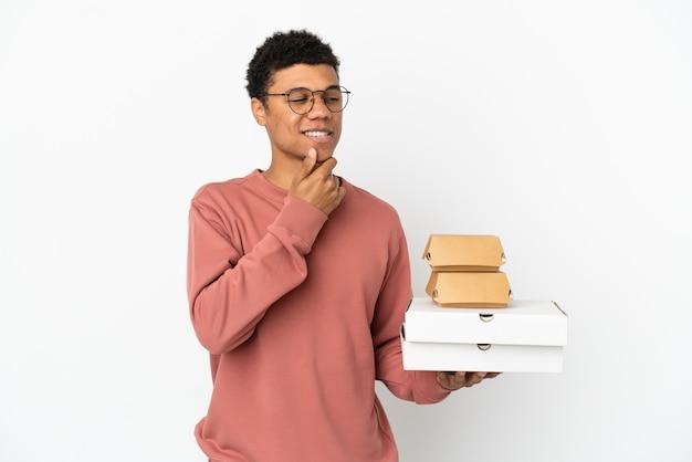 Junger afroamerikanischer mann, der einen burger und pizzas isoliert auf weißem hintergrund hält und zur seite schaut und lächelt